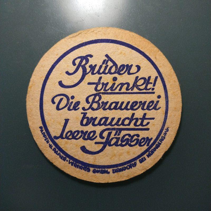 biervilt uit de jaren '50 met de tekst 'Brüder trinkt! Die Brauerei braucht leere Fässer'